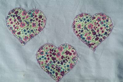 heart shaped fabric embellishing a plain duvet cover to repair a small hole