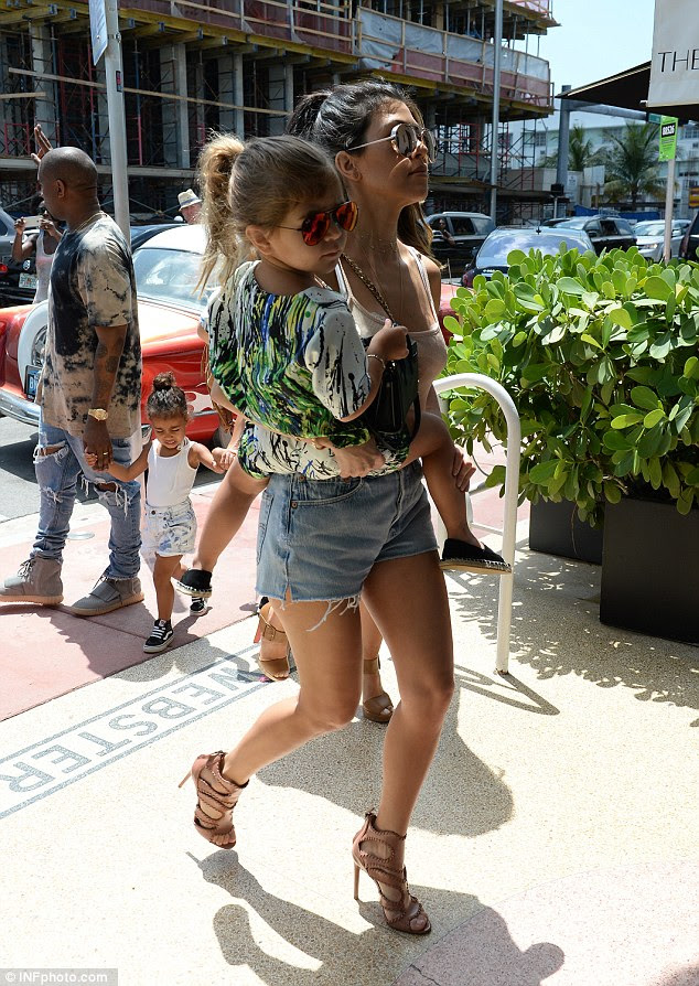 Fashion expedition: Kanye, who didn't seem to mind hanging out at the back of the entourage with his adorable two-year-old paused to wave at fans as they followed Kourtney into the trendy Webster boutique