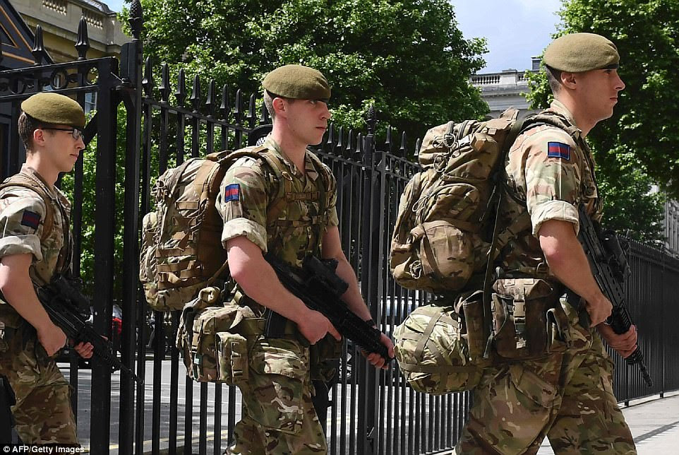 Pictures show troops arriving at a Ministry of Defence Building today. They had earlier been seen boarding buses at wellington Barracks in London after Theresa May raised the terrorism threat level in Britain to 'critical'