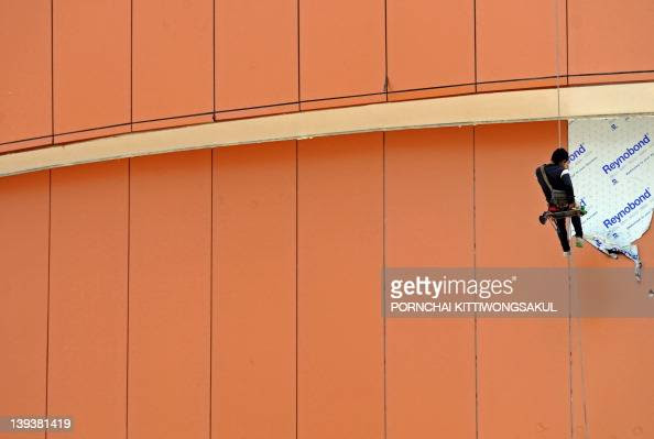 A Thai Worker Hangs Suspended As He Clea Pictures Getty Images