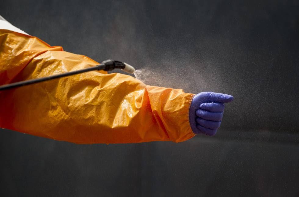 Un miembro del equipo de funerarios voluntarios en Guinea se desinfecta tras transportar el cuerpo de una fallecida por ébola. Enero de 2015.