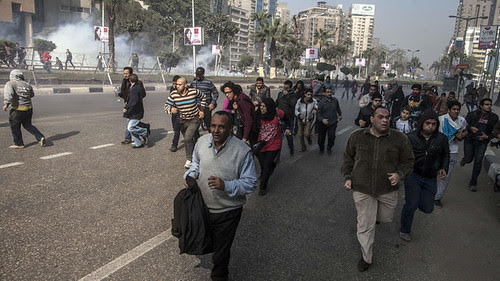 Egyptian anti-government protesters run for cover from tear gas during clashes with police in the capital Cairo on January 25, 2014 following a rally marking the anniversary of the 2011 uprising. by Pan-African News Wire File Photos