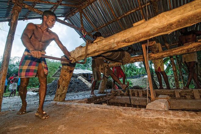 Mineiros operam manualmente polias para extrair terra numa mina rudimentar no Sri Lanka, à procura de pedras preciosas