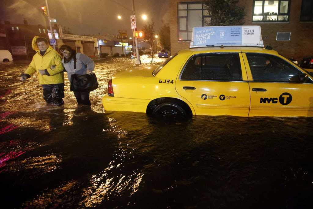 Pedestrians walk past a submerged taxi in Brooklyn, New York, as Hurricane Sandy made landfall in the northeastern United States. Hurricane Sandy began battering the U.S. East Coast on Monday with fierce winds and driving rain, as the monster storm shut down transportation, shuttered businesses and sent thousands scrambling for higher ground hours before the worst was due to strike.