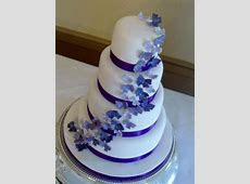 4 tier wedding cake with deep purple ribbon and cascading sparkly butterflies   Cakes