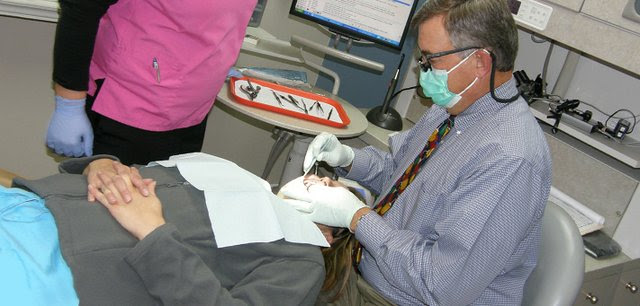 "Dave Hamel, one of three dentists in Marysville, examines a patient's teeth. Hamel, who's also president of the Kansas Dental Association, defended state laws that prohibit corporations from owning dental clinic. ""I think a dentist ought to be able to look at a patient and say 'What can I do for you? How can I be accountable for your care?' I don't know that you get that with corporate dentistry,"" he said. Also pictured: dental assistant Courtney Luedders and patient Amanda Foley."