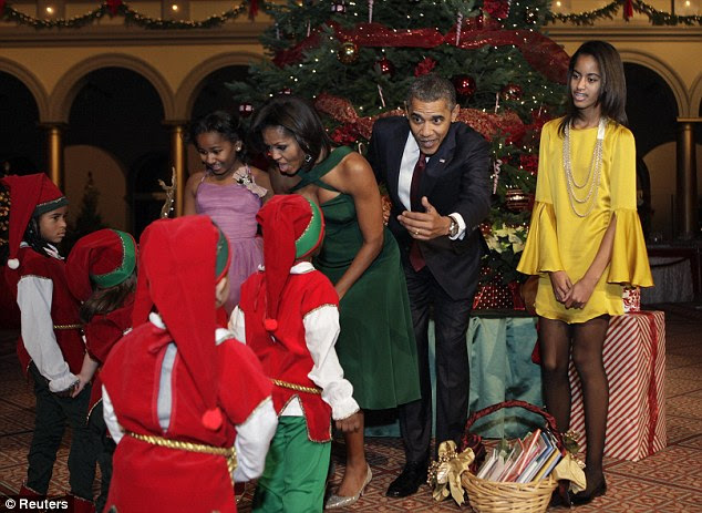 Santa's little helpers: Barack Obama and wife Michelle along with daughters Sasha (left) and Malia greet patients from the Children's Medical Center dressed as elves at the annual Christmas In Washington concert