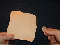 Obtain paper square and coin to perform this close up magic trick.