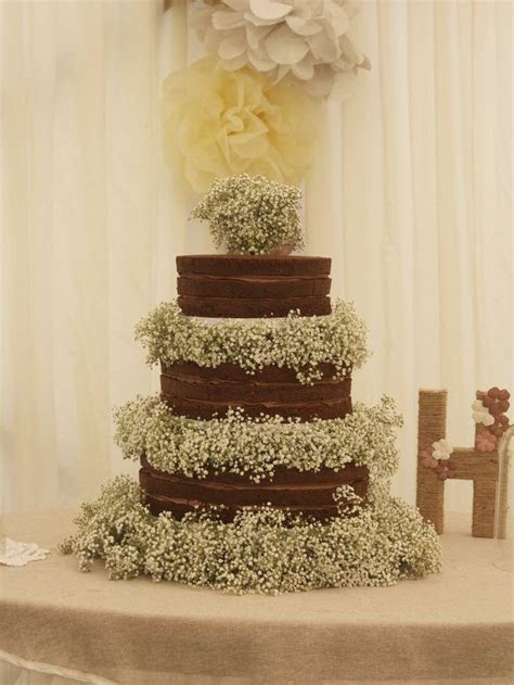 A large three tier naked chocolate wedding cake with fresh
