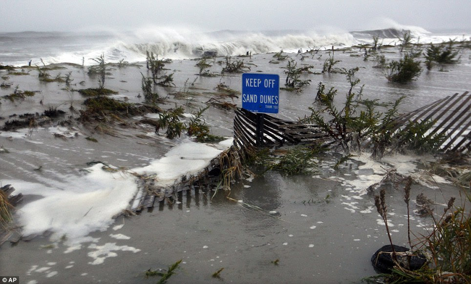 Keep away: Rough surf of the Atlantic Ocean breaks over the dunes on Monday morning in Cape May, New Jersey, as high tide and Hurricane Sandy begin to arrive