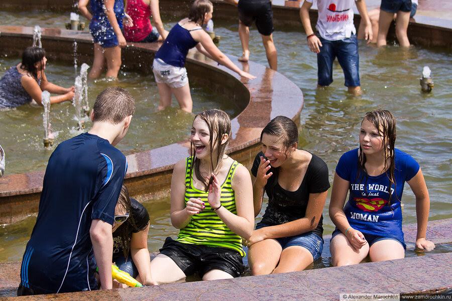 Девушки в мокрой одежде в фонтане