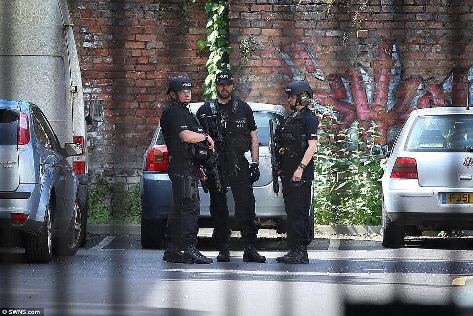 Oficiais armados guardam uma segunda propriedade invadida pela polícia hoje em Carlton Road, Manchester.  Um homem foi preso nas proximidades