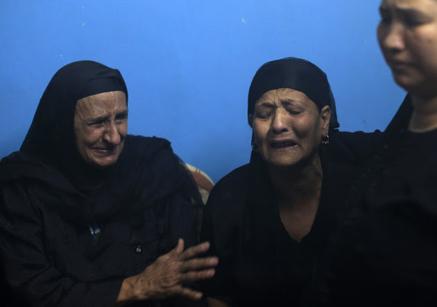 In this Monday, May 14, 2013 photo, Maria Sourial, center, mother of Romani Farhan Amir, mourns for her son at the family's home, some 180 miles (300 kilometers) south of Cairo in the province of Assiut, Egypt. Police say Amir, a 35-year-old laborer who did odd jobs for a day's wage, jumped to his death from a fourth-floor window in a court complex in Assiut, a city of 1 million people. His May 11 death came minutes before he was to be questioned by a judge on the stabbing and wounding nearly 12 hours earlier of his estranged wife, Azza William, who had vanished in January and reappeared the following month declaring she had converted to Islam. (AP Photo/Hassan Ammar)
