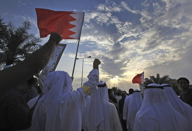 Bahraini pro-democracy protesters wave signs and pictures of prisoners and people killed in three years of unrest as well as national flags during a march in 2014