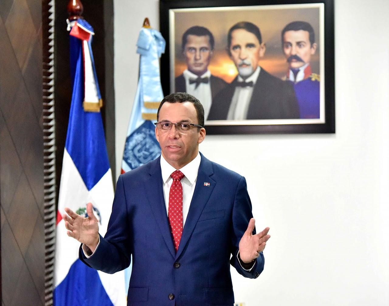 imagen Ministro Andrés Navarro de pie haciendo haciendo llamado a padres enviar sus hijos puntualmente a la escuela este lunes 07 de enero