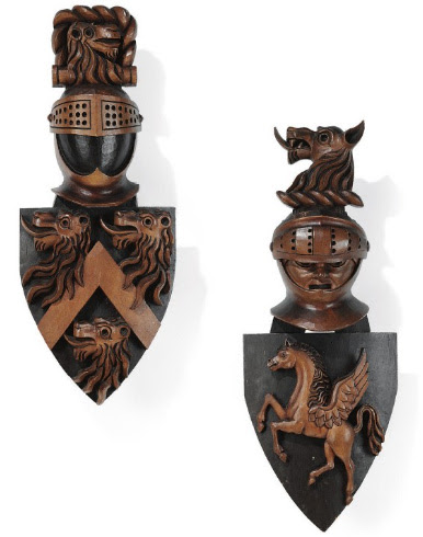 TWO IRISH 'ANTIQUARIAN' PAINTED PINE AND EBONISED ARMORIAL SHIELDS