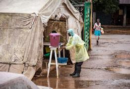 A health worker cleans his hands with chlorinated water before entering a Ebola screening tent, at the Kenema Government Hospital situated in the Eastern Province around 300 kilometer (186 miles) from the capital city of Freetown in Kenema, Sierra Leone, Monday, Aug. 11, 2014. (AP Photo/Michael Duff)