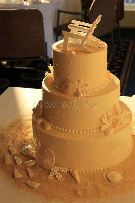 Three Layered Wedding Cake With Beach Theme On Table Stock