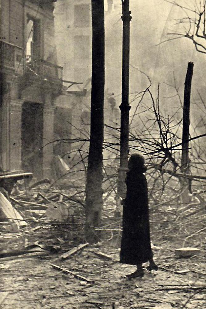 Una mujer camina entre escombros, durante la Guerra Civil.