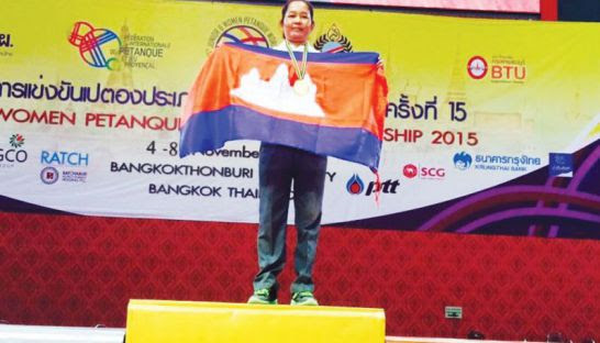 Ke Leng poses on the podium with her gold and the Cambodian flag at the 2015 Women's Petanque World Championships.