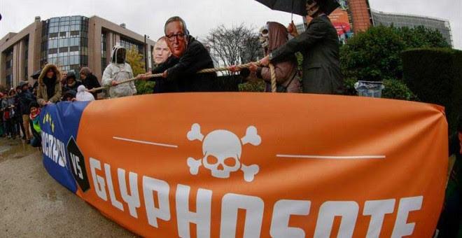 Activistas se congregan con máscaras del presidente de la Comisión Europea, Jean-Claude Juncker, y otros comisarios, en protesta contra el herbicida glifosato frente a la sede de la Comisión Europea en Bruselas. | OLIVIER HOSLET (EFE)