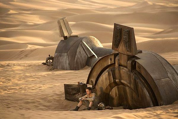 On the planet Jakku, Rey (Daisy Ridley) sits next to the foot of a downed AT-AT walker in STAR WARS: THE FORCE AWAKENS.