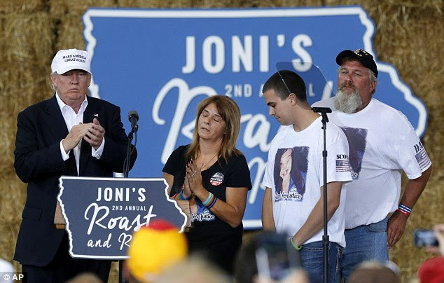 Republican presidential candidate Donald Trump shares the stage with the family of Sarah Root at Joni's Roast and Ride at the Iowa State Fairgrounds in Des Moines