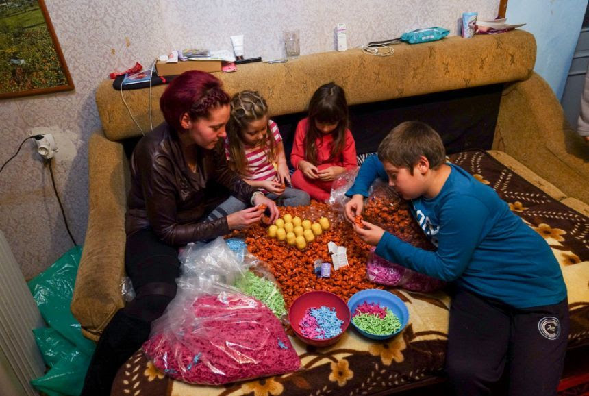 Femeia care apare în articolul The Sun asamblând jucării din ouă Kinder alături de copiii ei spune că totul este o înscenare. FOTO