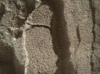 This view shows grains of sand where NASA's Curiosity Mars rover was driven into a shallow sand sheet near a large dune