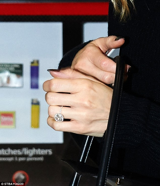 Dazzling: The model was spotted wearing a rather large diamond ring at the travel hub