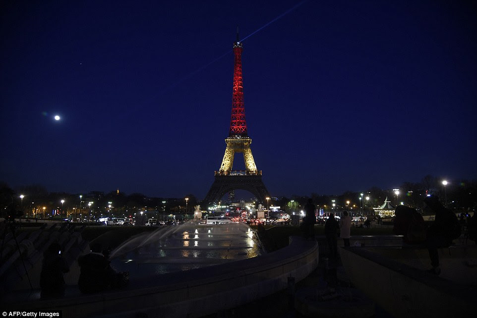 In mourning: The Eiffel Tower in Paris illuminated in colours of the Belgian flag in tribute to the victims of terrorist attacks in Brussels