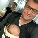 Selfie of Lipson holding baby in baby carrier on chest.