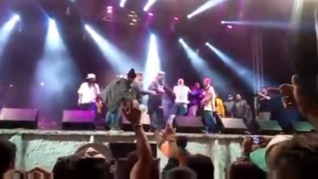 Cert (de camisa branca) é levado por policiais de cima do palco