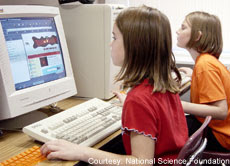 A photograph of children working at computers