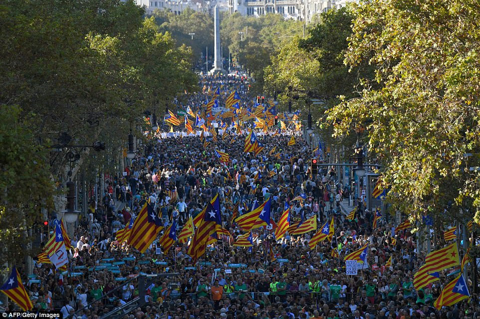 Protesters hold pro-independence Catalan Esteladas flags as they gather for a demonstration on earlier today in Barcelona