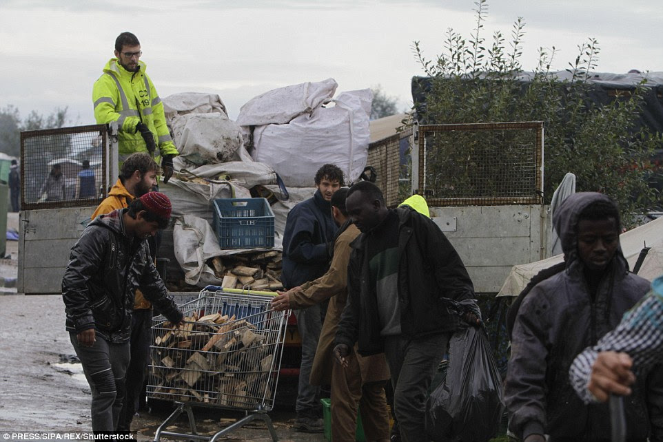 Refugees receive wood for heating and cooking from some volunteers as they carry bin bags