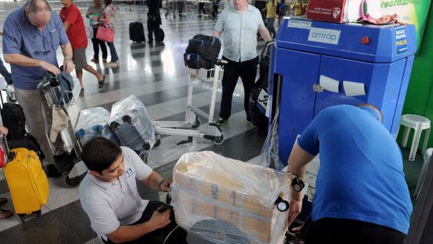 Passengers get their luggage wrapped in Manila airport on 4 November, 2015
