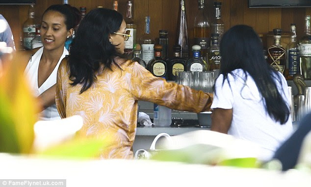 Staying hydrated:The glamorous pop star sported an outrageous pair of gold framed sunglasses as she was seen getting a bottle of Fiji water at the bar