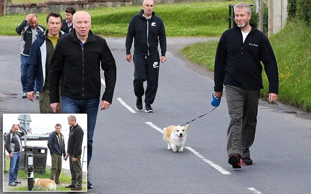 Roman Abramovich takes his pet corgi for a walk with FIVE security guards