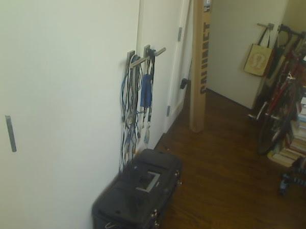 """""""Canto de um quarto com piso de madeira com uma caixa de ferramentas, uma bicicleta, uma pilha de livros, uma caixa encostada na parede, uma porta aberta com uma bolsa pendurada na maçaneta e uma porta dupla fechada com cabos pendurados"""" (Foto: Matt Richardson)"""