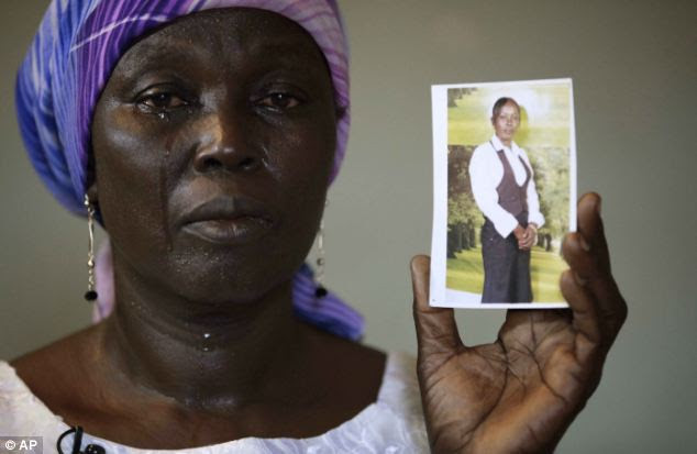 Martha Mark holds up a photograph of her daughter Monica who is one of the girls kidnapped by Boko Haram