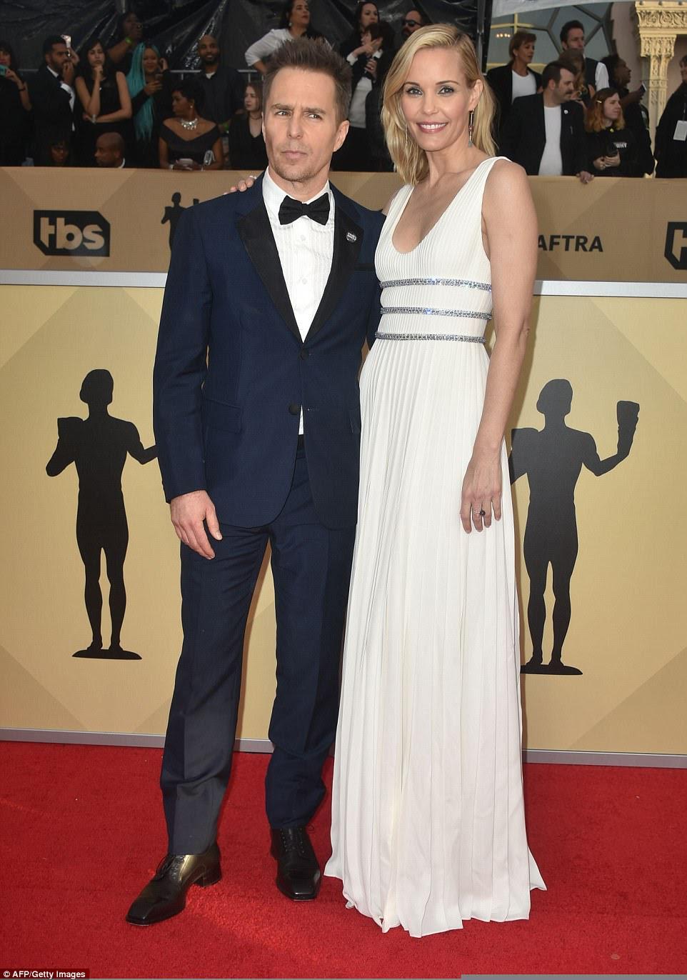 Então, no amor: Sam Rockwell e Leslie Bibb sorriram no tapete;  Leslie observou seu número branco e prateado