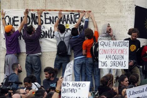 Un grupo de jóvenes cuelgan una pancarta en la Puerta del Sol. | J. Barbancho
