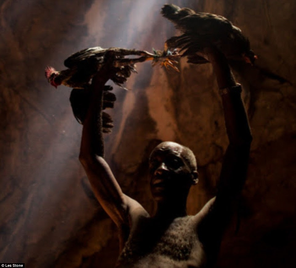 A sign of respect and dedication: Inside the Cave of St Frances, a man is preparing to sacrifice two chickens to spirits in front of crowds