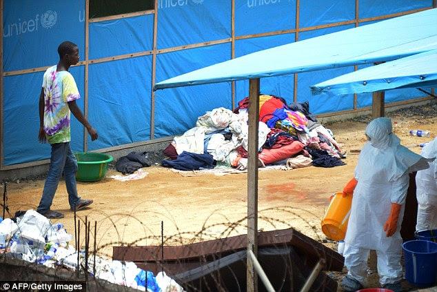 Um homem suspeito de estar contaminado com o vírus Ebola passa por um trabalhador vestindo um terno de Equipamentos de Proteção Individual (EPI) de hoje dentro da zona de alto risco em quarentena do hospital John Fitzgerald Kennedy, na capital da Libéria, Monróvia