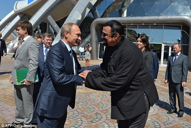 Russian President Vladimir Putin shakes hands with movie actor Steven Seagal at the Russia's first ever Eastern Economic Forum (EEF) in Vladivostok
