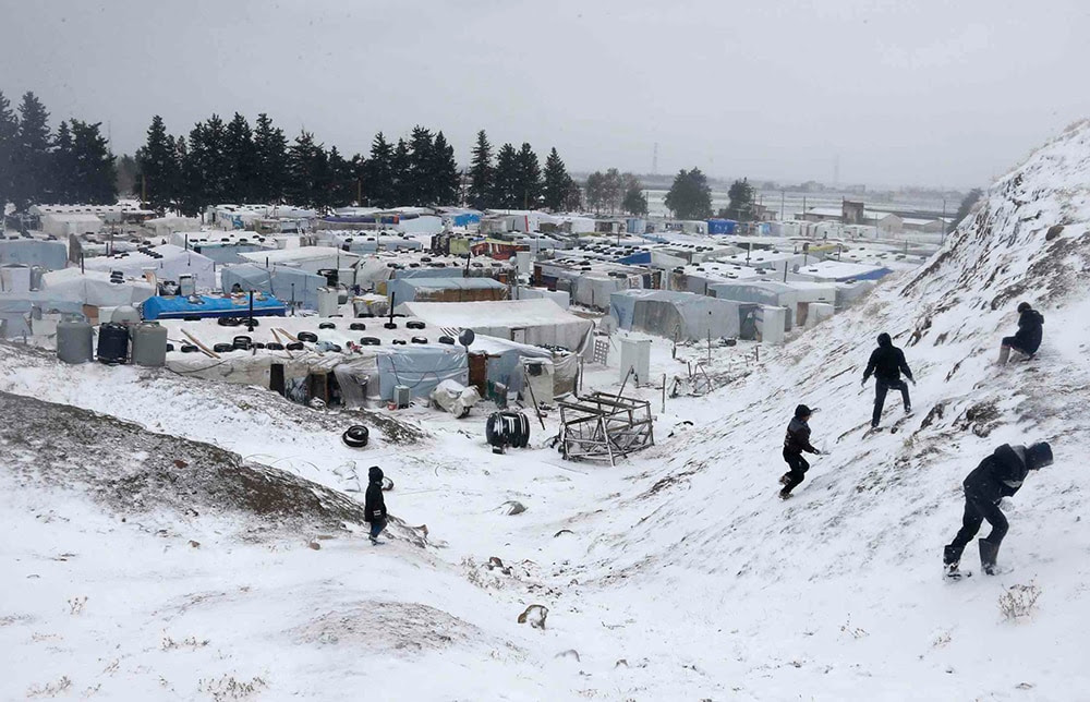 Syrian refugees play with snow during a winter storm in Zahle town, in the Bekaa Valley. (REUTERS/Mohamed Azakir)