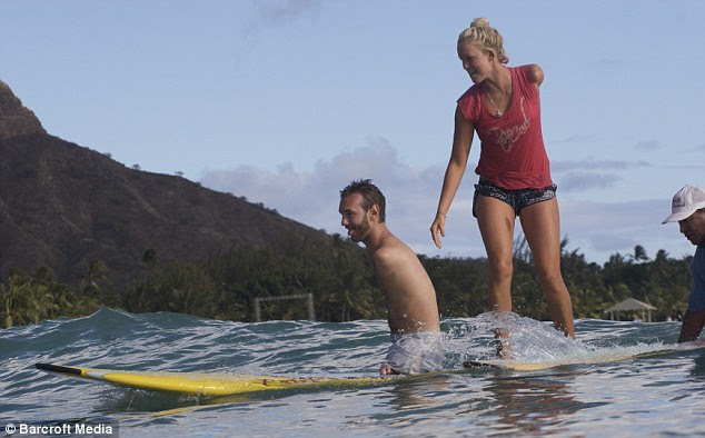 Bethany Hamilton teaches Nick how to surf in Hawaii in 2008. Bethany got her arm bitten off by a shark when she was a teenager - and was back on a surfboard within three weeks.