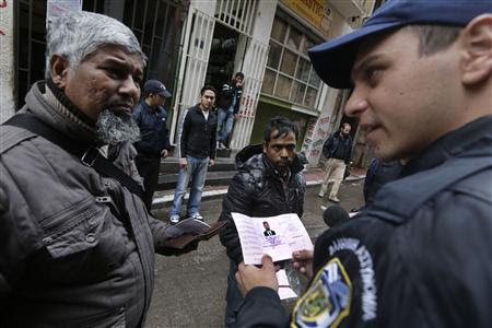 A police officer checks immigrants' documents during an operation in the centre of Athens December 5, 2012. REUTERS-John Kolesidis