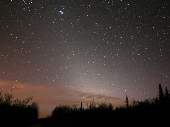 Zodiacal light tilts upward from the western horizon and points at the Pleiades star cluster in this photo taken March 19, 2009. Clouds at bottom reflect light pollution from nearby Duluth, Minn. U.S. Credit: Bob King